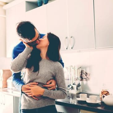 man woman kiss in kitchen