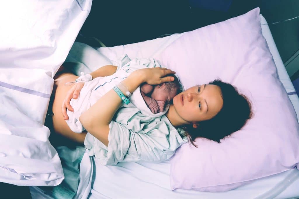 mother with newborn in hospital bed