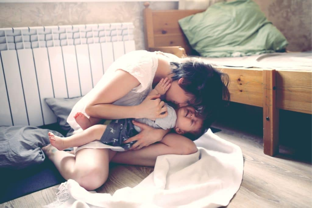 mother kiss baby in room
