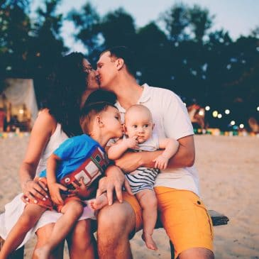 family kiss on beach