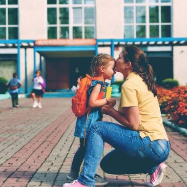 mother kiss kid back to school
