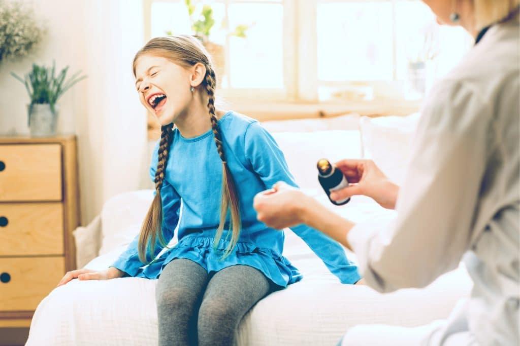 little girl unhappy cough syrp