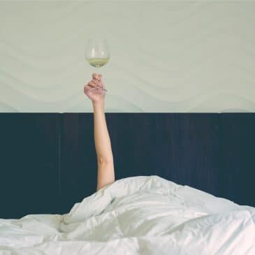 woman in bed with wine