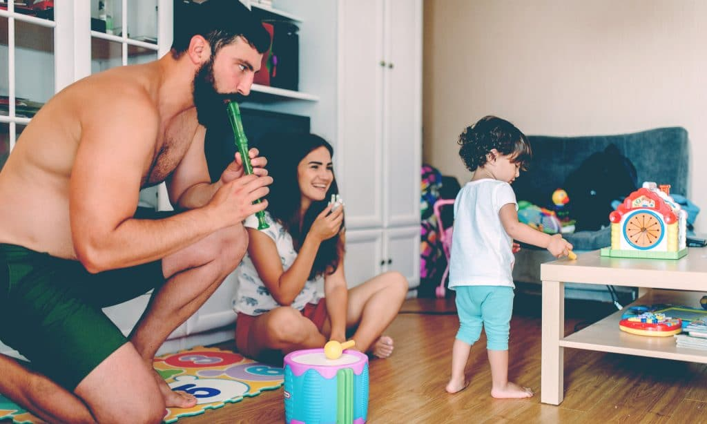man play with kids in living room