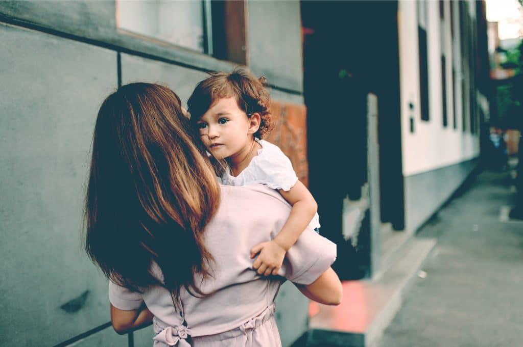 woman hold kid on street
