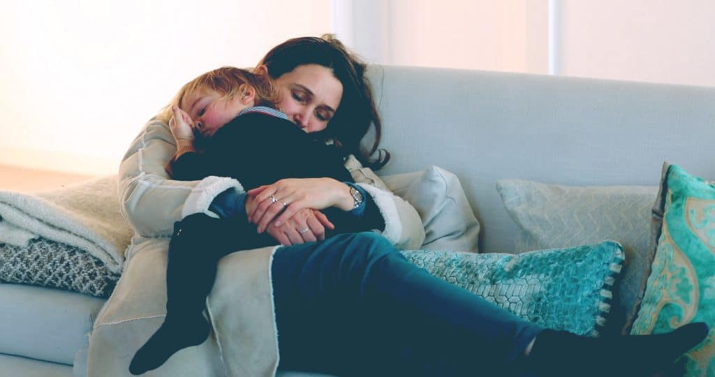 mother hold kid on couch