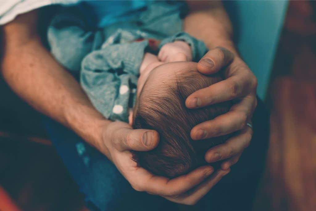 father hold newborn