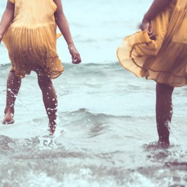 two friends jumping in water