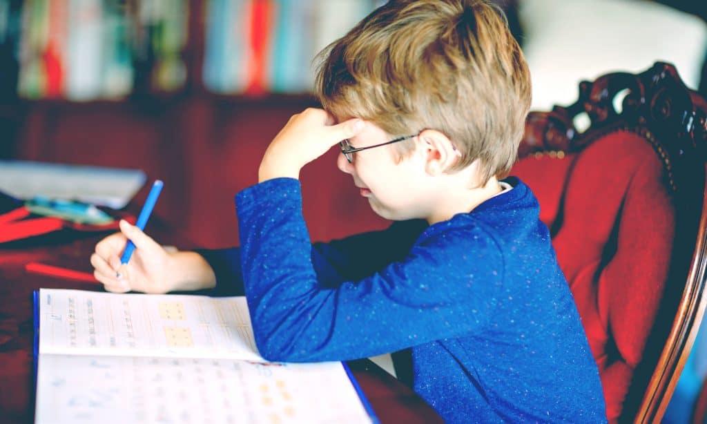 sad kid doing homeworks