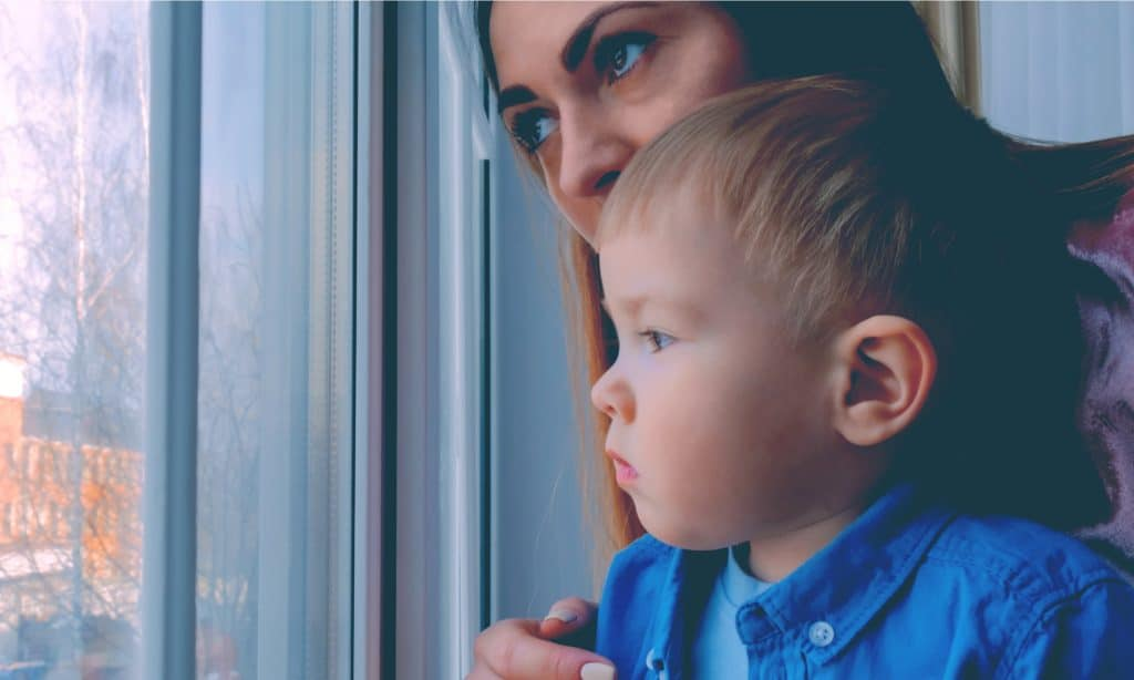 sad mother and son look at window