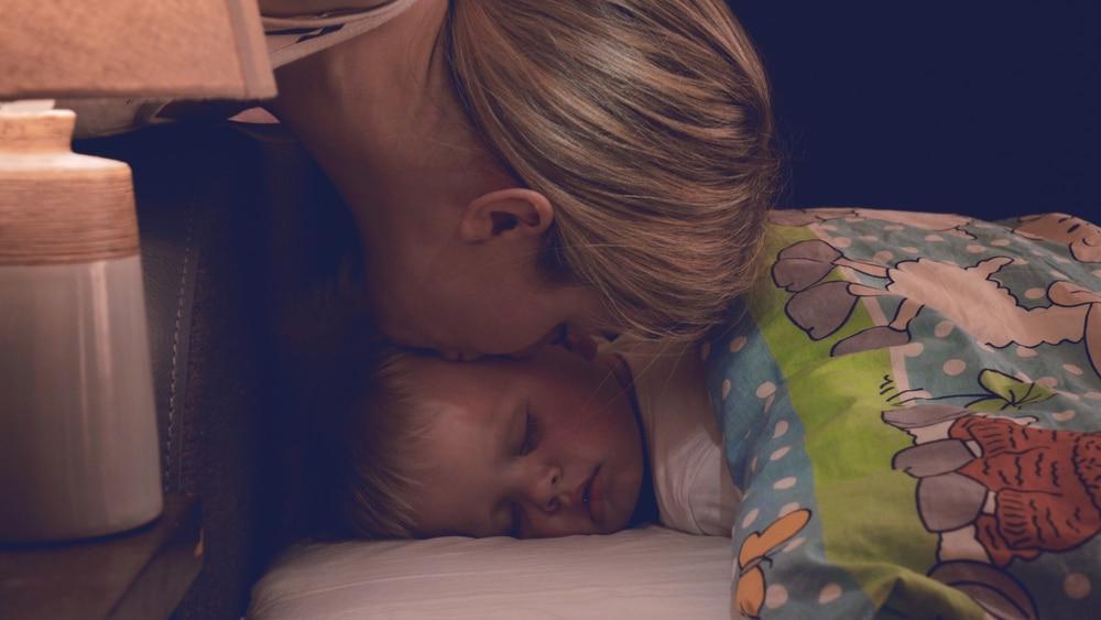 mother kiss kid at night