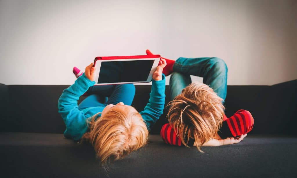 two kids play on tablet