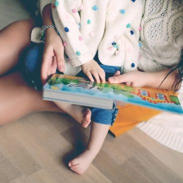 mother reading book with kid