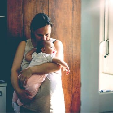 tired mother with newborn at home