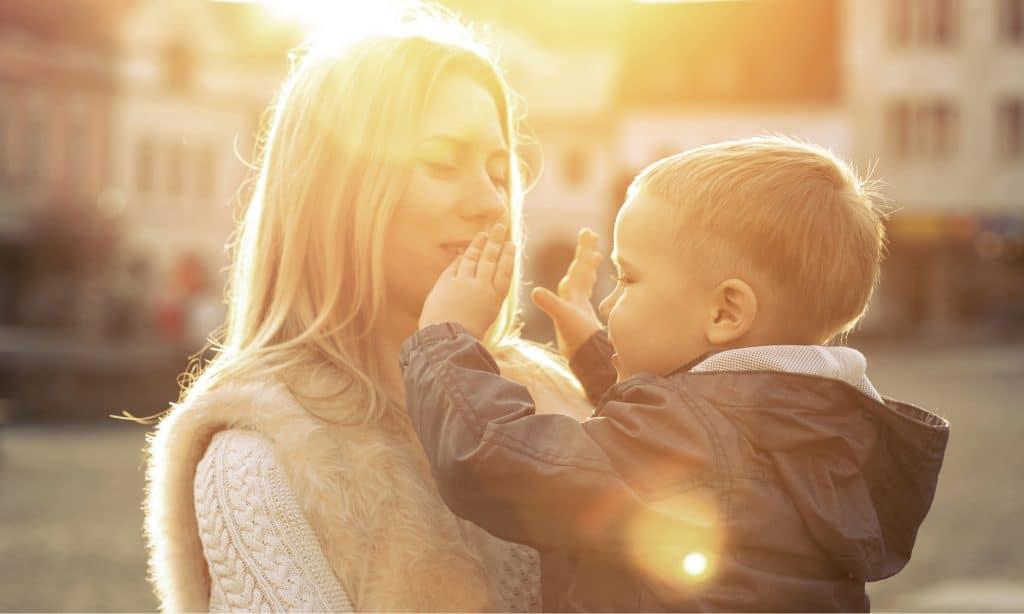 mother kiss kid sun