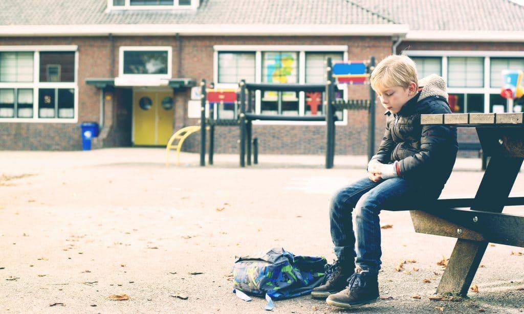 sad boy alone at school