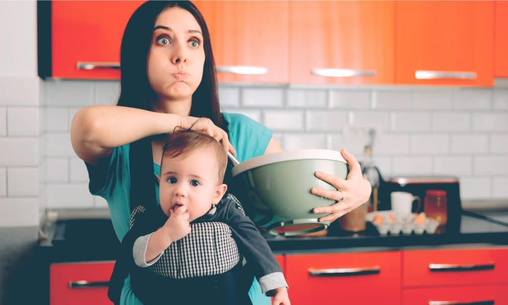 tired mother with baby in kitchen
