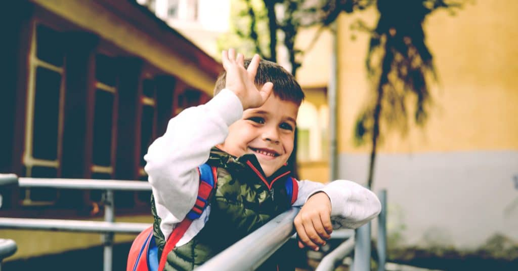little boy say goodbye at school