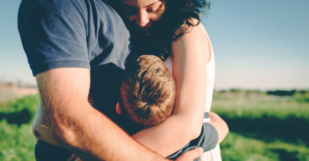 father mother and kid hug