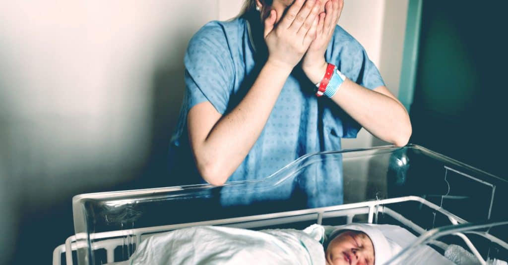 sad mother baby delivery hospital