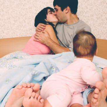 mother father and baby in bed