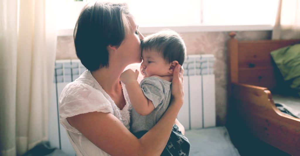 mother kiss little kid at home