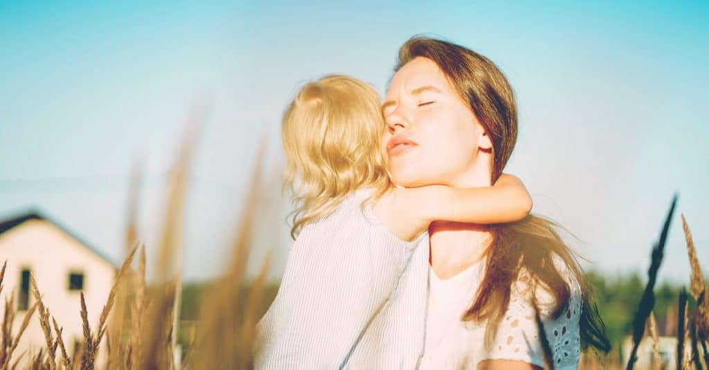 mother hold baby in a field