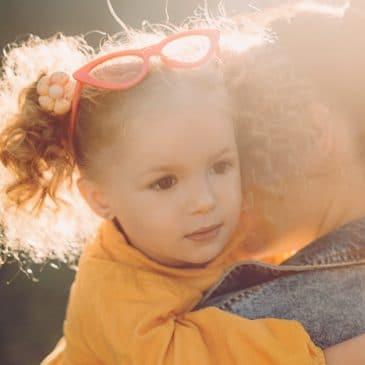 mother hold little girl sun