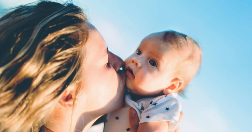 mother kiss baby sky