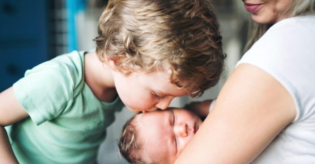 toddler kissing baby brother