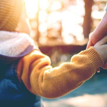 woman hold kid's hand